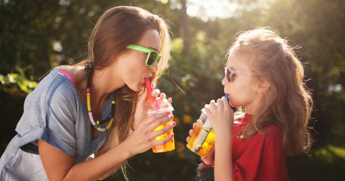 Mother and young daughter wearing sunglasses and drinking tea outside