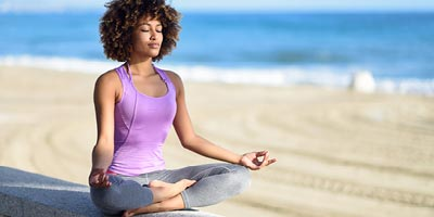 African American woman in the purple tank top doing yoga peacefully on the beach.
