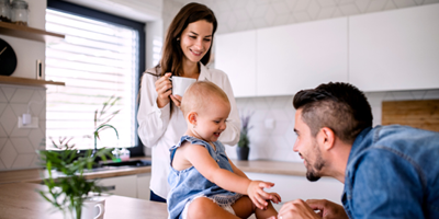 Young mom and dad playing with their baby who is sitting on the kitchen counter.