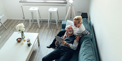 Senior couple on their couch as they browse a tablet for information on Medicare.