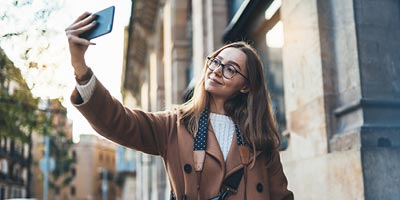 Woman on a cold day making a selfie with her phone.