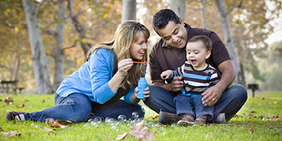 Couple outside blowing bubbles with their baby boy.