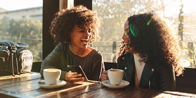 Two young African American women laughing and talking at a coffee shop.