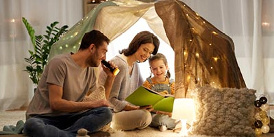 Mom, dad and their young daughter camping in a tent in the living room and reading a book.