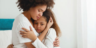 Mom hugging young daughter, looking very sad.