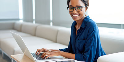 African American woman with glasses looks up and smiles as she types on her laptop.