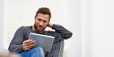 Man with a beard and a gray shirt studying something on a tablet.