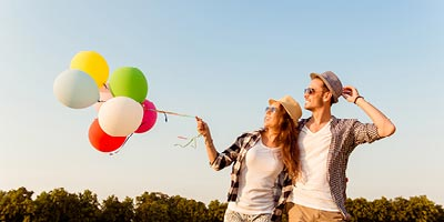 Young couple walking together holding colorful balloons that are flying in the wind.