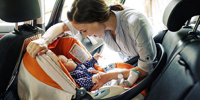 Young mother fastening her baby's carseat into the car and smiling at her baby.
