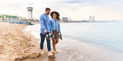 A smiling couple walks together along a beach with a cityscape in the background.