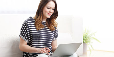 A woman in a striped shirt smiles as she works on her computer.