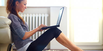Woman sitting on the floor of her living room, smiling, looking at her computer.
