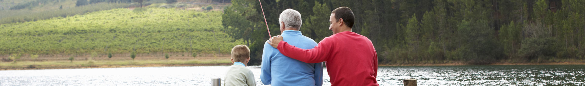 Adult son fishing with elder father and young son symbolizing families that are caring for aging parents and young children.