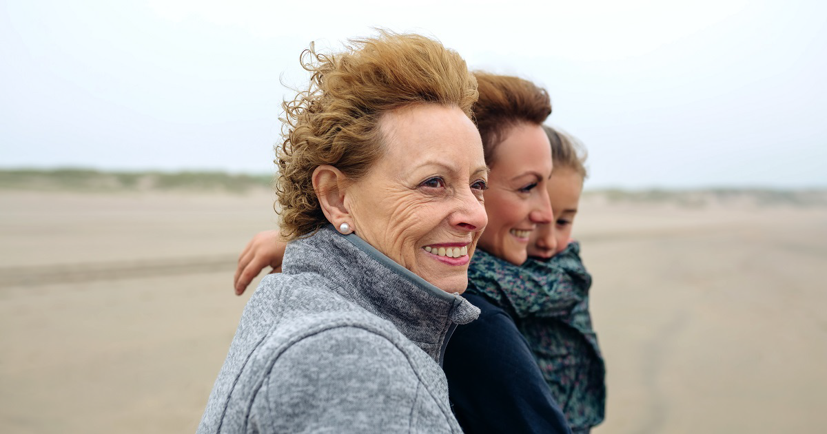 Grandmother standing with daughter and grandaughter on a windy beach.
