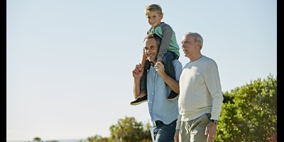 Grandfather, father and son walking outside near ocean