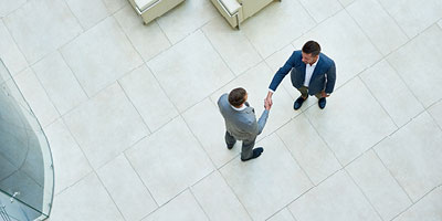 An overhead image of two businessmen shaking hands in an office lobby.