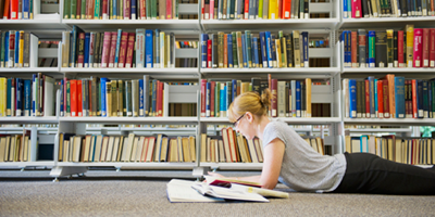 A female college student studies on the floor of the library.
