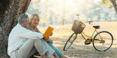 A senior adult couple resting after a bike ride and discussing their last will and testament plans.