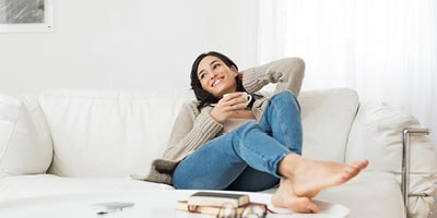 Young woman smiling and relaxing on her living room couch with a cup of coffee.