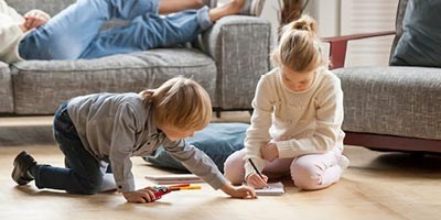 Brother and sister sitting on living room floor writing and playing