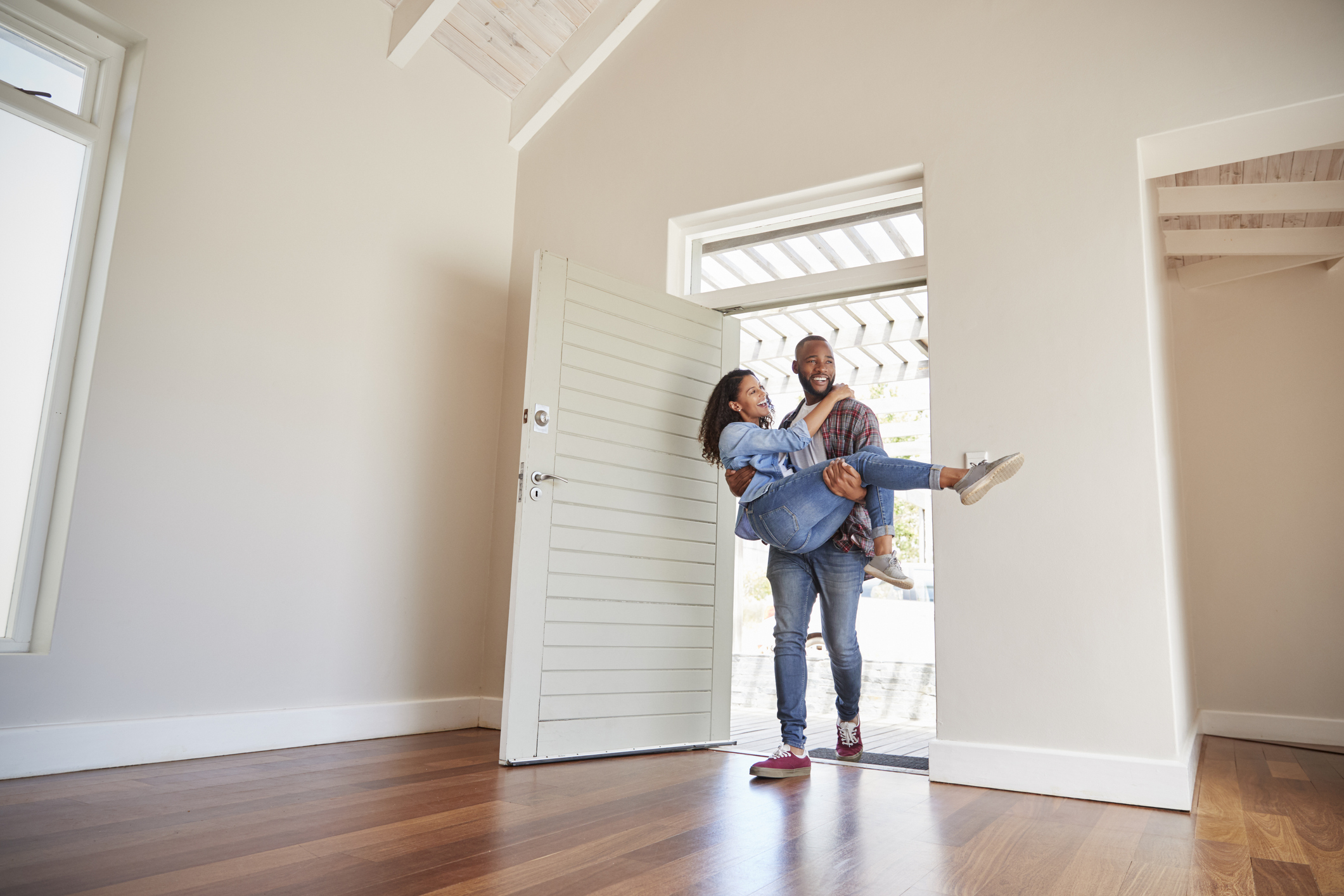 A man carries his wife over the threshold and into their new home.