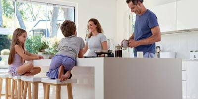 Dad and mom make breakfast in white modern kitchen while son and daughter sit on barstools at counter