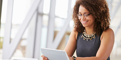Woman in her 20s smiling and looking at an iPad.