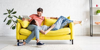 Young couple on yellow couch discussing homeownership