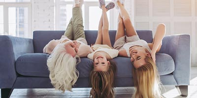 Laughing mom and two teenage daughters lie upside down on blue couch