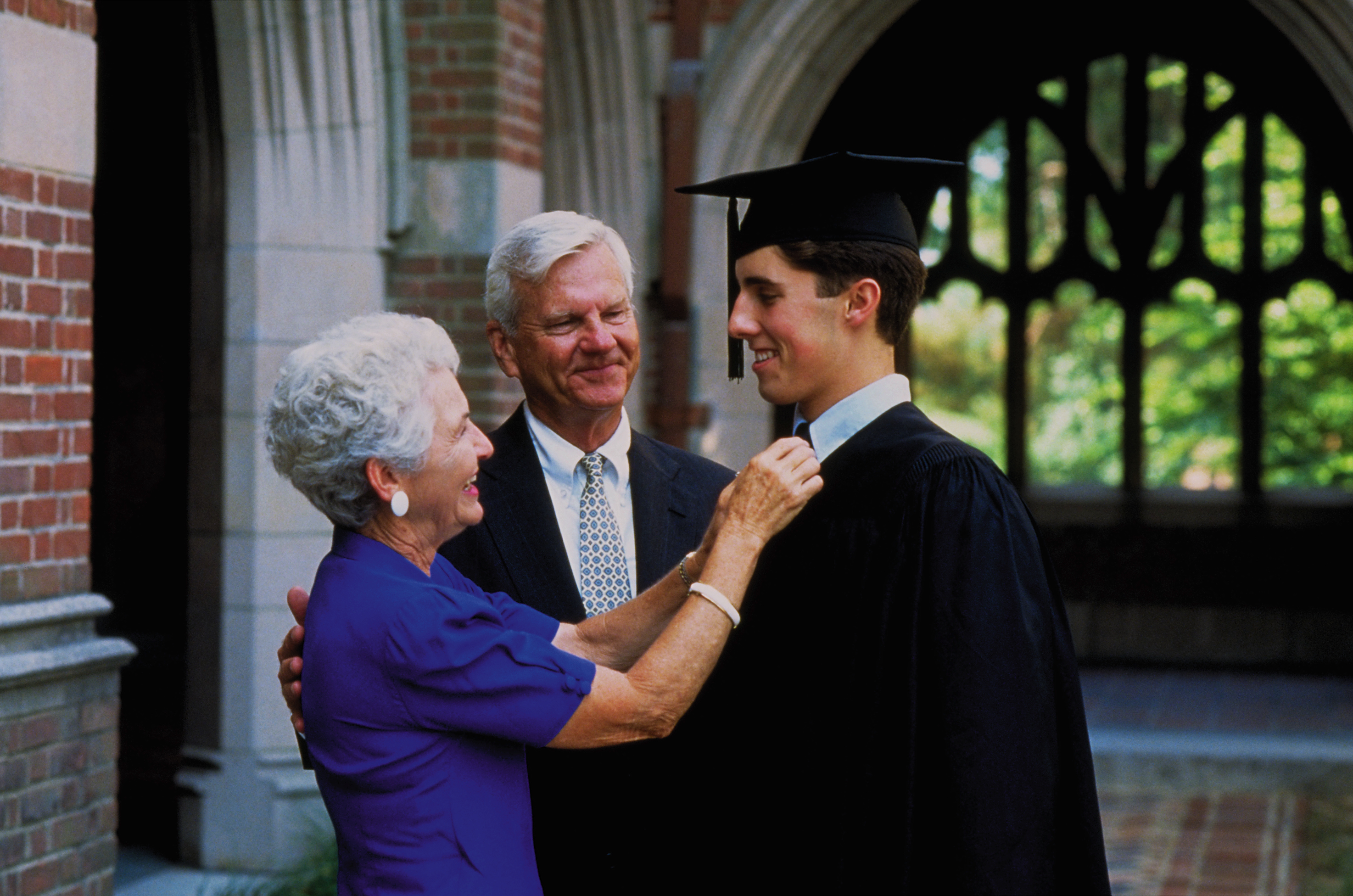 Proud parents talk with their son at his college graduation.