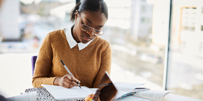 Young African-American woman studying at college so she can pay off her student loans upon graduation.