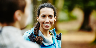 Female young adult smiling while chatting with a friend in nature.