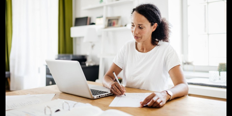 Woman sitting at desk with laptop and binder of papers