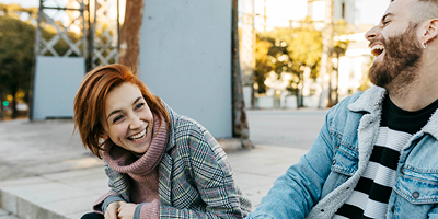 Young female and male student sitting outside together and laughing.