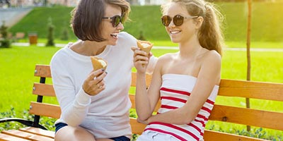 Mother and daughter eating ice cream and discussing how teens can learn to budget