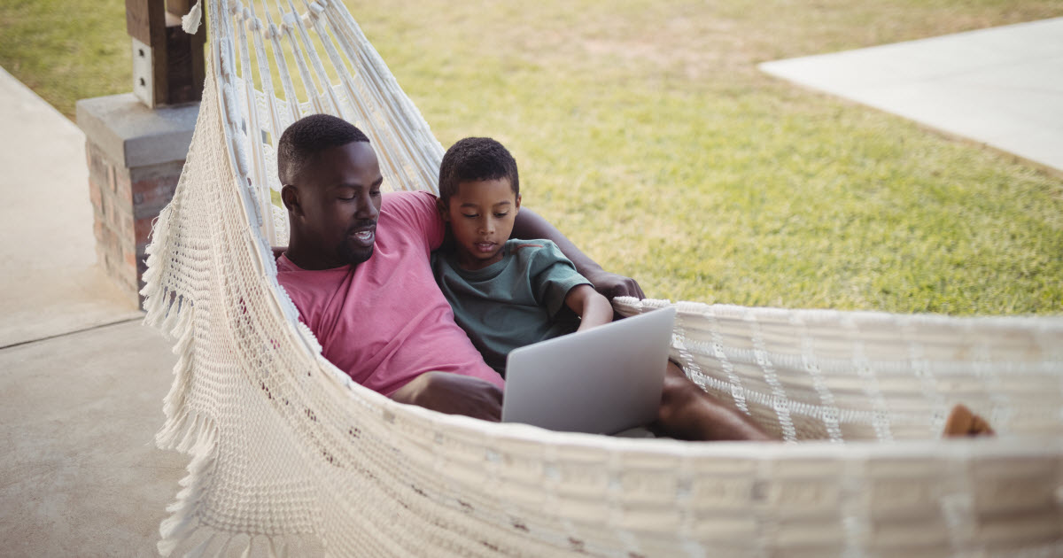 Father and son in hammock looking at laptop