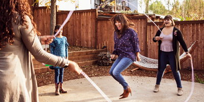 A mom with three adolescent and young girls trying to jump rope with them.