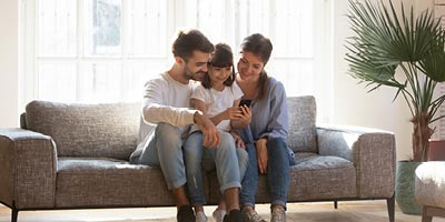 Picture of mom and dad sitting on the living room couch with their young daughter in-between, looking at a mobile phone.