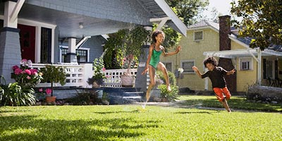 Two bi-racial children playing in sprinkler in front of their home.