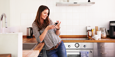 Woman standing in her kitchen and browsing information on her smartphone.