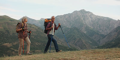 Older man hiking in the mountains with walking sticks and a backpack.
