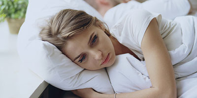 Woman looking very depressed lying in bed and staring into space.