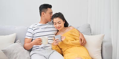 Newlywed couple sitting together while drinking coffee resting assured that they have life insurance.