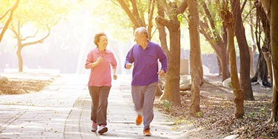Older couple running in park; they may be candidates for life insurance that covers a funeral or burial expenses.