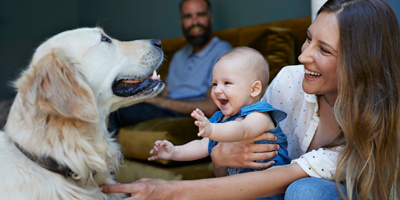 Young couple sitting in their living room with a dog and baby.