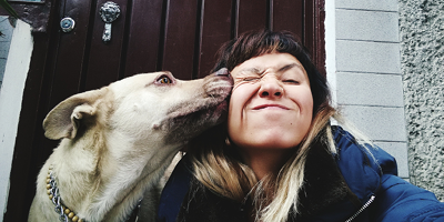 Photo of woman with her dog licking her face, sitting on the front stoop of her house.