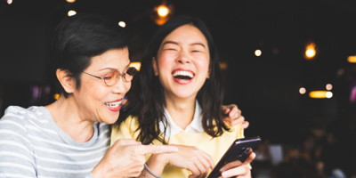Asian mom and her daughter laughing together while looking up something on a mobile phone.