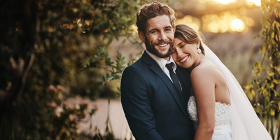 A newlywed couple at their wedding, thankful that they have planned well for their finances.