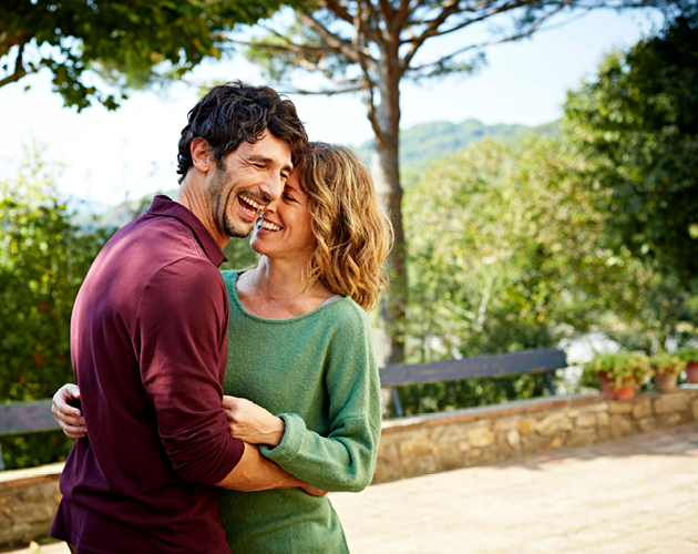 Husband and wife laughing and embracing outdoors.