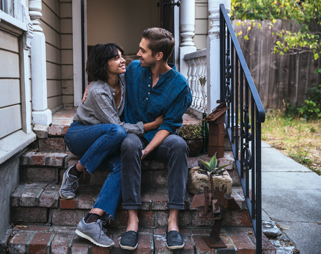 Young couple sitting on steps of first home.